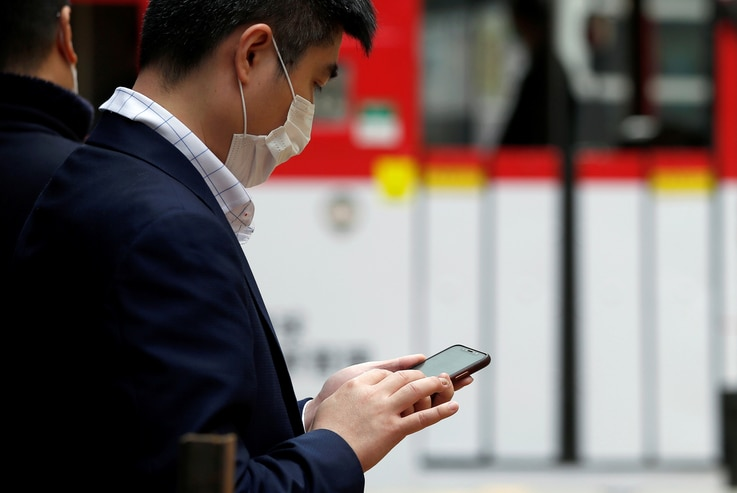 A man wears a protective mask as he looks at his mobile phone, following the outbreak of the new coronavirus, in Hong Kong,…