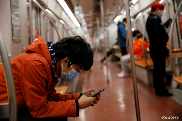 FILE PHOTO: A man wearing a face mask checks his mobile phone while riding a subway in the morning after the extended Lunar New…