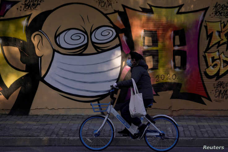 A woman wearing a protective mask cycles past graffiti-painted wall at a construction site in Shanghai, China, as the country…