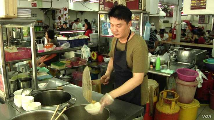 """Alex Lee runs a wonton noodle stall at a popular open air food court in Kuala Lumpur. Lee, a smoker for two-decades, supports enforcement of the smoking ban at all eateries nationwide. """"People should have clean air while they eat,"""" he says."""
