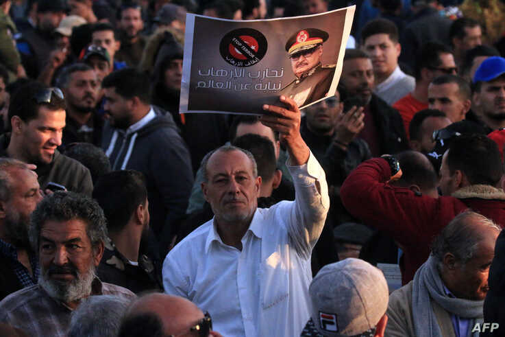 FILE - Supporters of Libyan military strongman Khalifa Haftar (image) take part in a demonstration in Benghazi, eastern Libya, against what they see as Turkey's intervention in their country's affairs, Feb. 14, 2020.