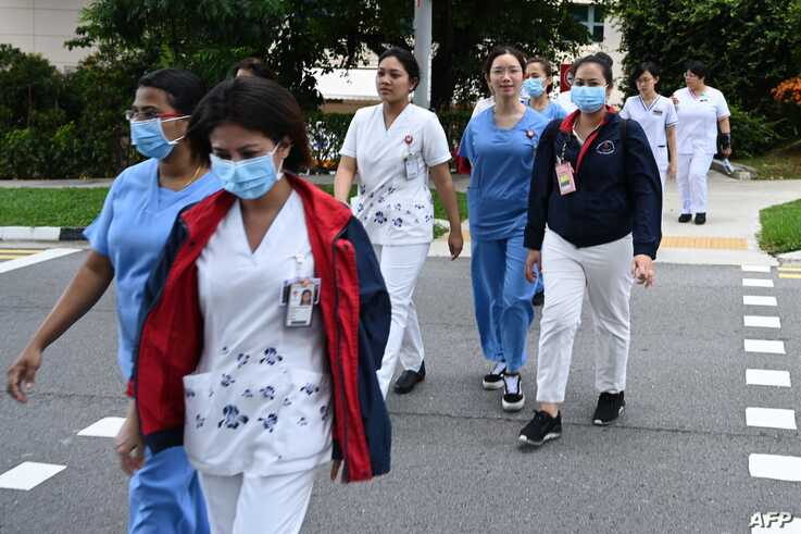 FILE - Medical staff are seen walking to the National Centre for Infectious Diseases building, at Tan Tock Seng Hospital, in Singapore, Jan. 31, 2020.