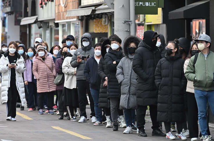 People wait in line to buy face masks at a store in the Dongseongro shopping district in Daegu, South Korea. South Korea reported 334 new coronavirus cases, taking its total to 1,595, still the largest in the world outside China.