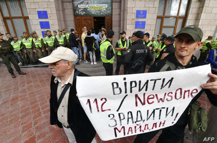 """FILE - Activists protest against TV channels they see as agents of Russian disinformation, in Kyiv, Sept. 5, 2019. Their sign reads """"To believe TV channels '112' and 'NewsOne' is to betray the 'Maidan' (Ukraine's revolution of dignity)."""""""