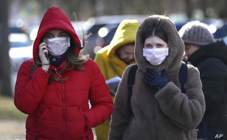 People wearing protective masks walk on street in Minsk, Belarus, Feb. 28, 2020. Belarus, Lithuania and New Zealand have reported their first cases of coronavirus.