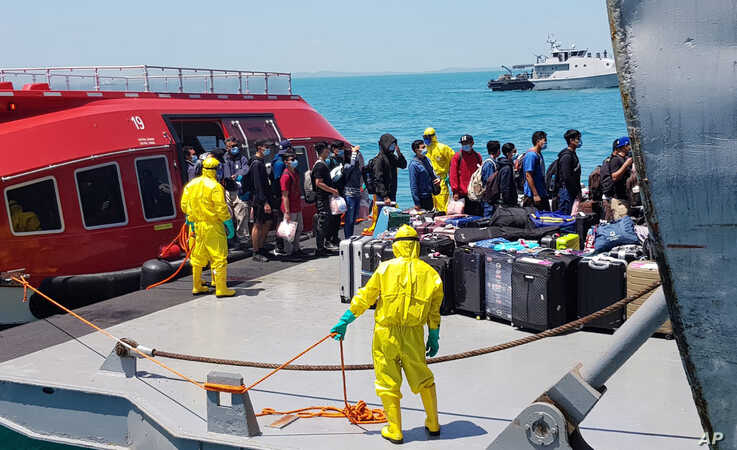 In this photo released by the Indonesian military, personnel in protective suits help unload the belongings of Indonesian crew members from the World Dream cruise ship as they are transferred to a hospital ship near Durian Bay, Indonesia, Feb. 26, 2020.