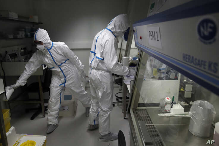 French lab scientists in protective suits work on developing a quick test for detecting the coronavirus, at Pasteur Institute in Paris, France, Feb. 6, 2020.