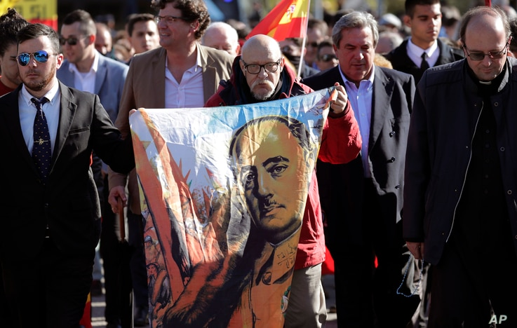 FILE - A man holds a cloth with a depiction of the late Spanish dictator Francisco Franco, during the reinterment of his remains, outside Mingorrubio's cemetery, on the outskirts of Madrid, Spain, Oct. 24, 2019.