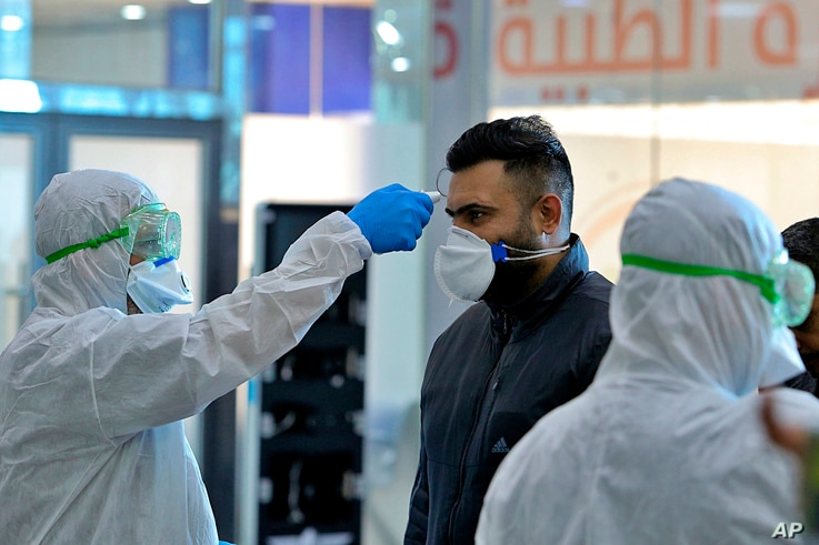Medical staff check temperature of passengers arriving from Iran in the airport in Najaf, Iraq, Feb. 21, 2020.