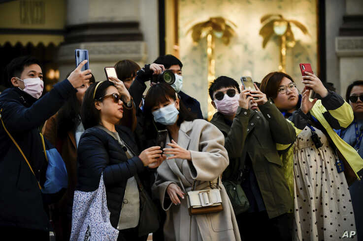 People, some wearing protective masks amid a coronavirus outbreak, take photos in central Milan, Italy, Feb. 24, 2020.
