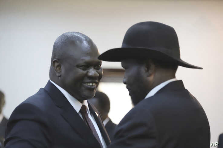 South Sudan President Salva Kiir, right, and opposition leader and now Kiir's deputy, Riek Machar, congratulate each other after a swearing-in ceremony in Juba, South Sudan, Feb. 22, 2020.
