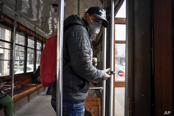 A man wearing a protective mask steps off an empty tram in downtown Milan, Italy, Feb. 26, 2020.