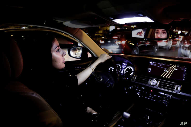 FILE - A Saudi woman drives her car down busy Tahlia Street in Riyadh, Saudi Arabia, June 24, 2018.