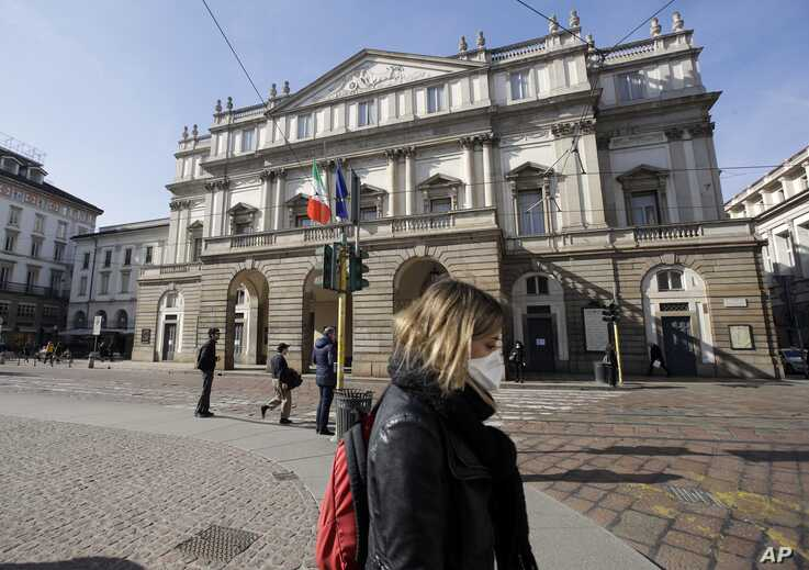 FILE - A woman wearing a protective mask walks past La Scala Opera house in Milan, Italy, Feb. 24, 2020.