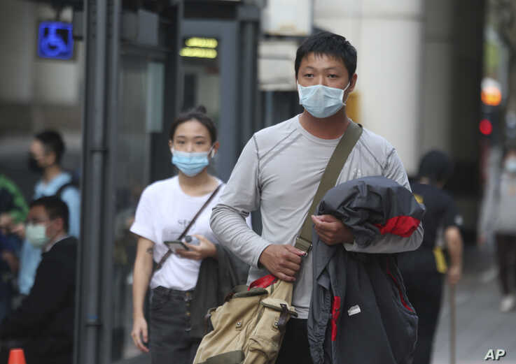 People wear face masks to protect against the coronavirus, in Taipei, Taiwan, Feb. 26, 2020.