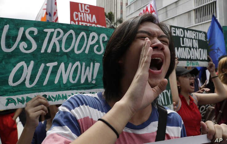 FILE - Protesters shout slogans as they march near the U.S. Embassy in Manila, Philippines, marking Independence Day, June 12, 2019. Among the demonstrators' demands was an an end to the Visiting Forces Agreement with the United States.
