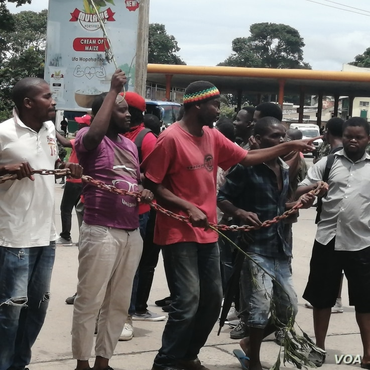 Protestsers carry a chain to be used to shutter the Malawi Electoral Commission office in Blantyre, Malawi. (Lameck Masina/VOA)