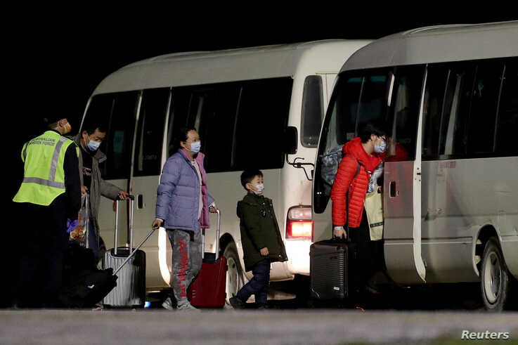 FILE - Australian evacuees from China's Wuhan, the epicenter of the coronavirus epidemic, board a bus after arriving at the airport on Christmas Island, Australia, Feb. 6, 2020.