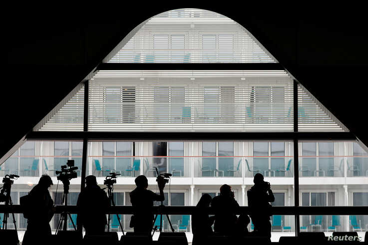 Journalists work near the World Dream cruise ship after it had been denied entry in Taiwan amid concerns of coronavirus infection on board, at the Kai Tak Cruise Terminal in Hong Kong, Feb. 6, 2020.