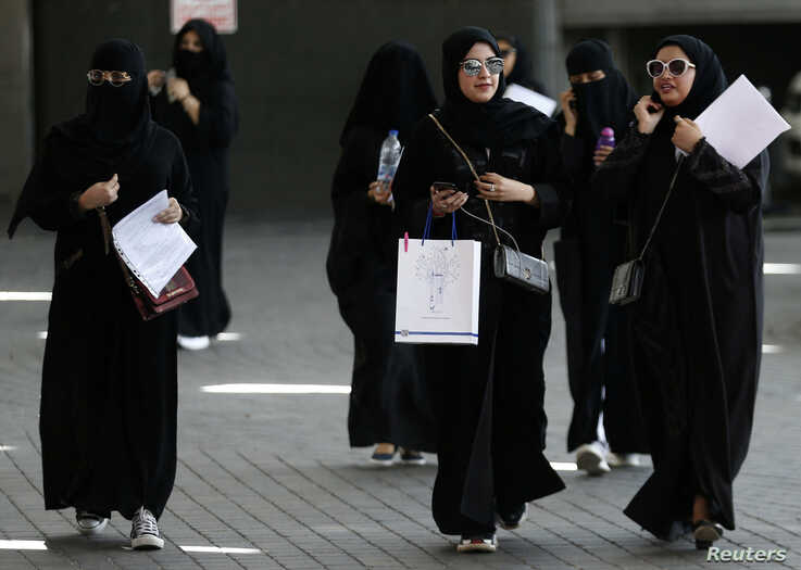 FILE - Female Saudi students walk at a job seekers fair in Riyadh, Saudi Arabia, Oct. 2, 2018.