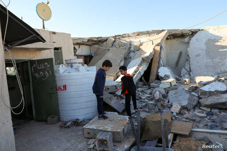 Boys stand near a damaged house after shells fell on a residential area, in Abu Slim district, south of Tripoli, Libya, Feb. 28, 2020.