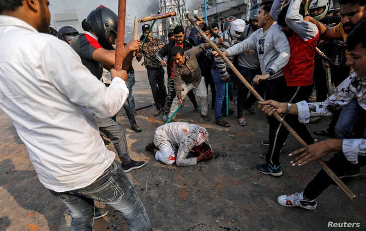People supporting the new citizenship law beat a Muslim man during a clash with those opposing the law in New Delhi, India, Feb. 24, 2020.