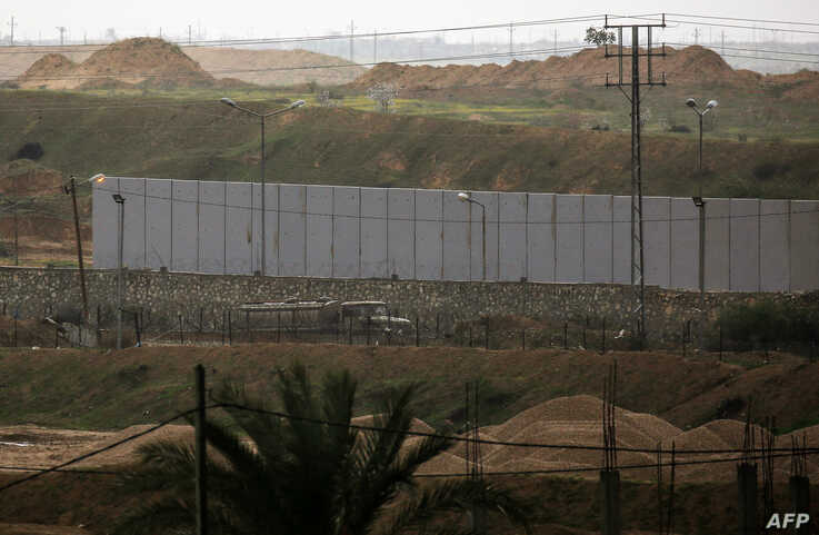 A picture taken in Rafah in the southern Gaza Strip at the border with Egypt shows a concrete wall under construction on the…