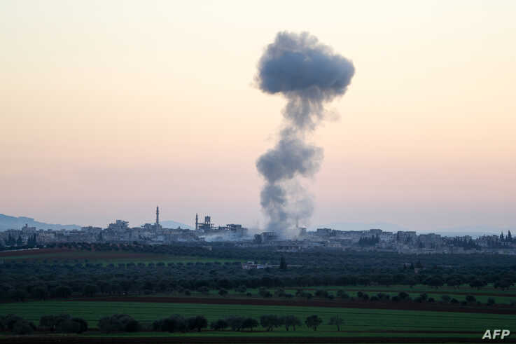 Smoke billows above the rebel-controlled village of Sarmin near the regime-held town of Saraqeb, in the eastern part of the…