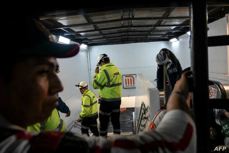 Metro personnel remain at the entrance of the Tacubaya station, where two trains collided leaving one dead and 41 injured, in…