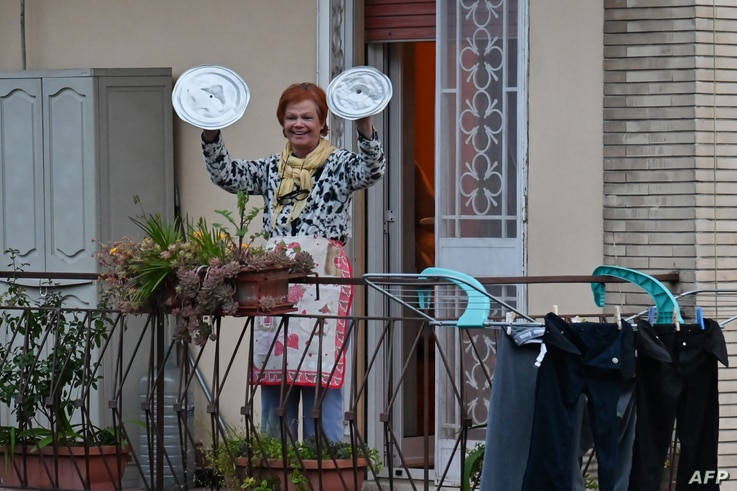 "A residents uses pot lids to play cymbals as she takes part in a music flash mob called ""Look out from the window, Rome mine !""…"