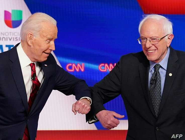 Democratic presidential hopefuls former US vice president Joe Biden (L) and Senator Bernie Sanders greet each other with a safe…