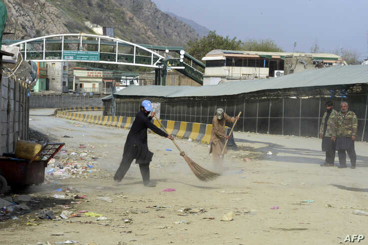 Workers clean a street near the closed Pakistan-Afghanistan border amid concerns over the spread of the COVID-19 novel…