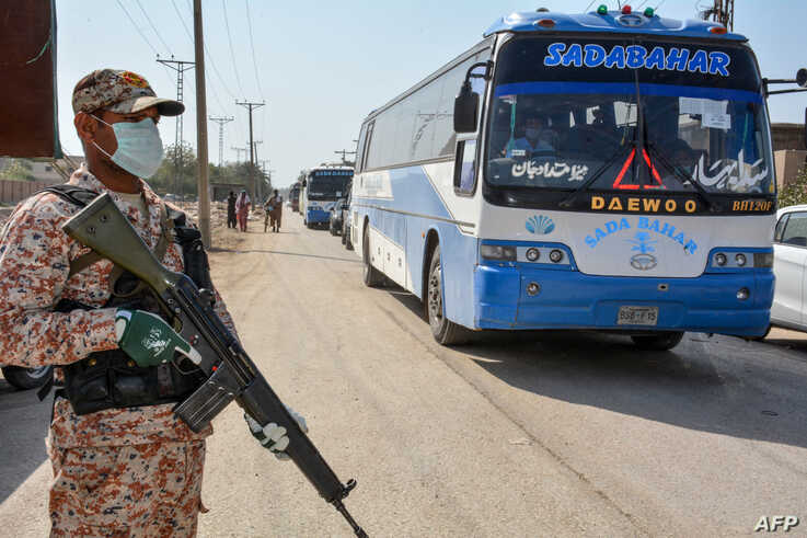 A soldier wearing a facemask stands guard as buses carry pilgrims returning from Iran via the Pakistan-Iran border town of…