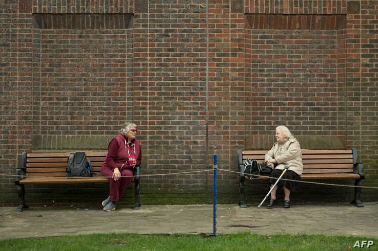 Two women observe social distancing measures as they speak to each other from adjacent park benches amidst the novel…