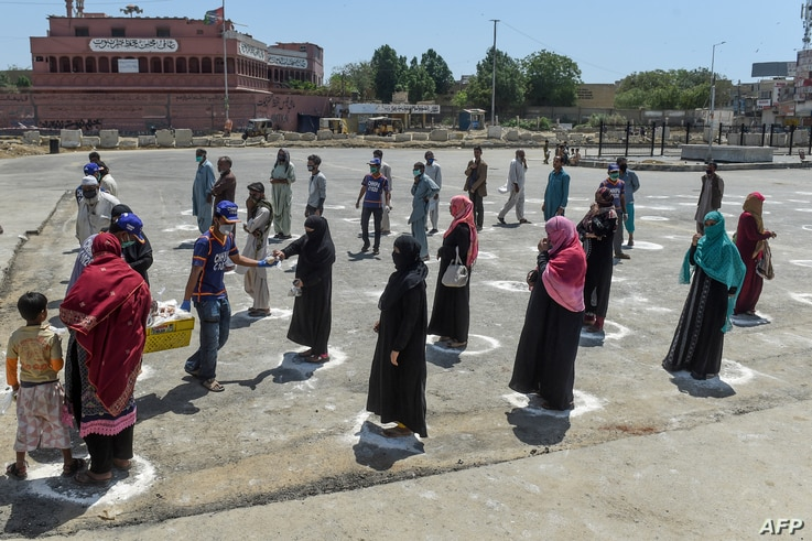 People stand in designated areas marked on the ground to maintain social distanciation as they receive free food from…
