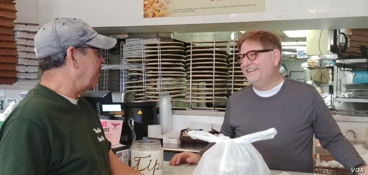 Primo Family Restaurant owner Jim Nicopoulos gives carryout food to a customer. (Deborah Block/VOA)