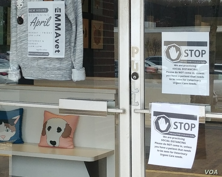 Sign on the door at emergency veterinarian EMMAvet requesting social distancing from customers.