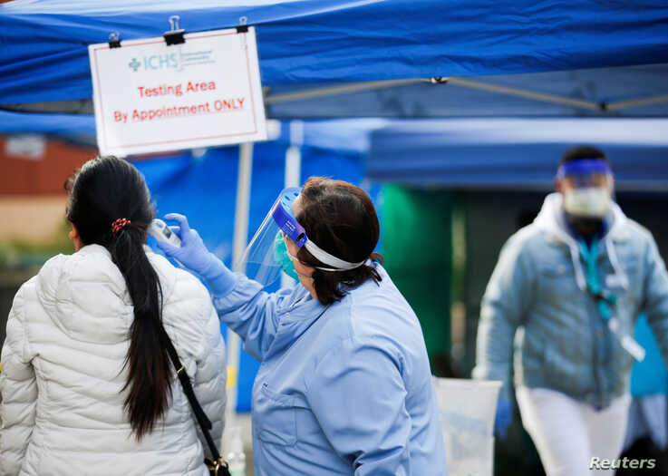 A person gets their temperature checked before entering International Community Health Services in Seattle
