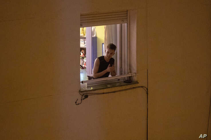 A man applauds from his window in support of the medical staff in Madrid, Spain, March 15, 2020.