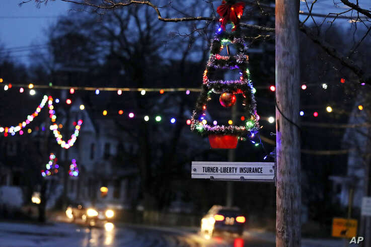 In this March 19, 2020, photo, a lit Christmas tree hangs from a pole at dusk as holiday lights illuminate downtown in Farmington, N.H.