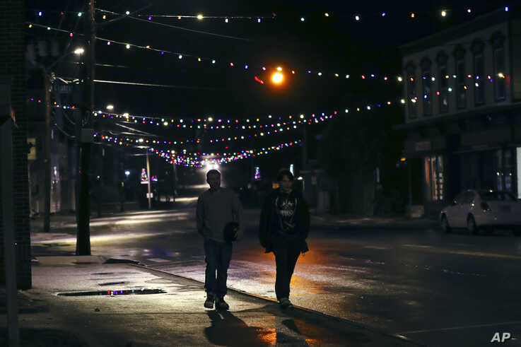 Two young men walk down Main Street under Christmas lights through downtown in Farmington, N.H., March 19, 2020.