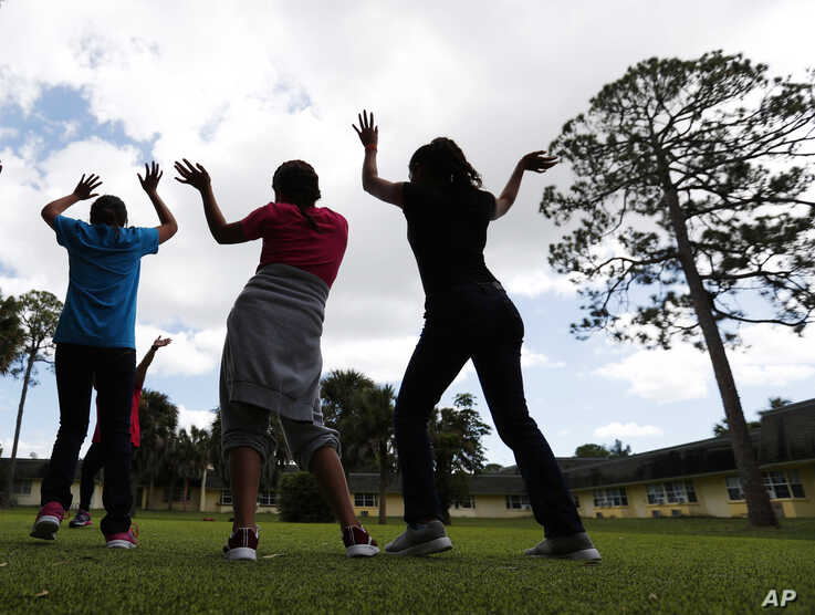FILE - In this Sept. 24, 2019, file photo, girls dance as they do exercises at a shelter for migrant teenage girls, in Lake…