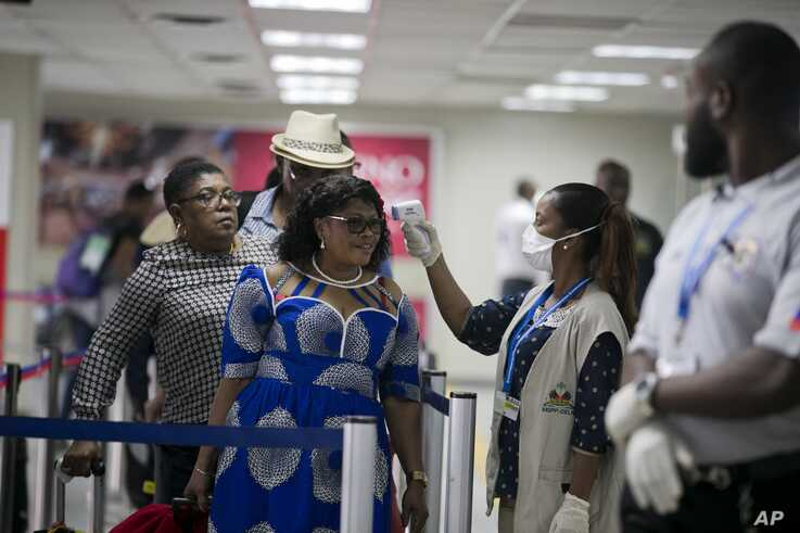 A Public Health Ministry nurse measures the temperature of a passenger arriving from France, at the Toussaint Louverture airport