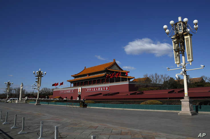 FILE - In this Feb. 16, 2020, file photo, a masked paramilitary policeman stands guard alone at a deserted Tiananmen Gate…