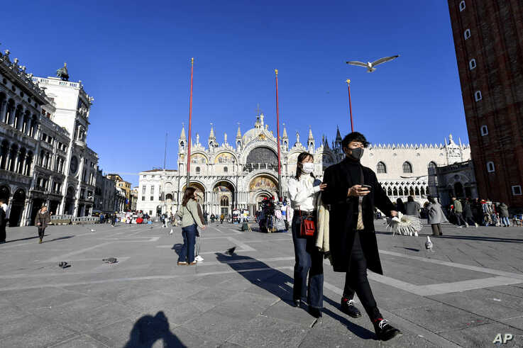 Tourists walk in St. Mark's Square in Venice, Italy, Feb. 28, 2020.