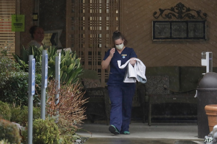 A worker at the Life Care Center in Kirkland, Wash., near Seattle, wears a mask as she leaves the building, Monday, March 2, 2020.