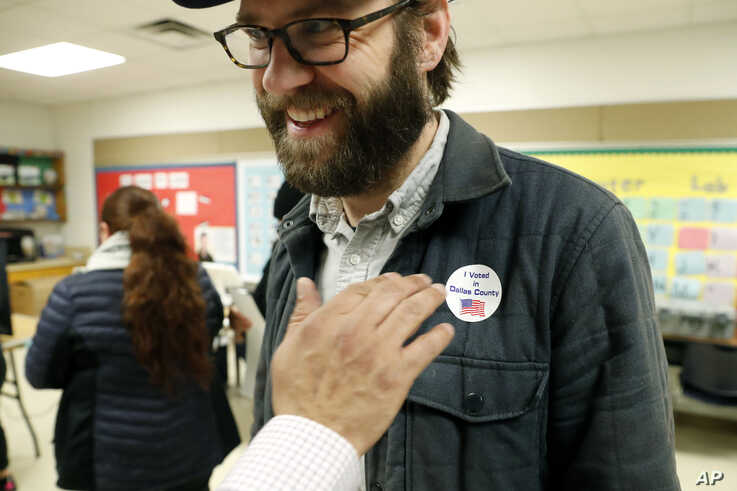 Democrat Jamie Wilson gets a sticker after voting in the Super Tuesday primary at John H. Reagan Elementary School in the Oak…