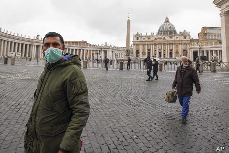 A man wearing a mask walks in St. Peter's Square at the Vatican, March 6, 2020.