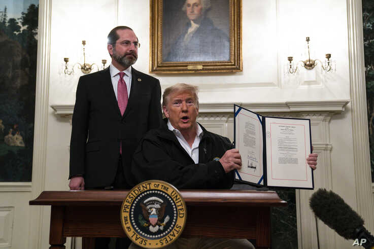 Secretary of Health and Human Services Alex Azar looks on as President Donald Trump shows a spending bill
