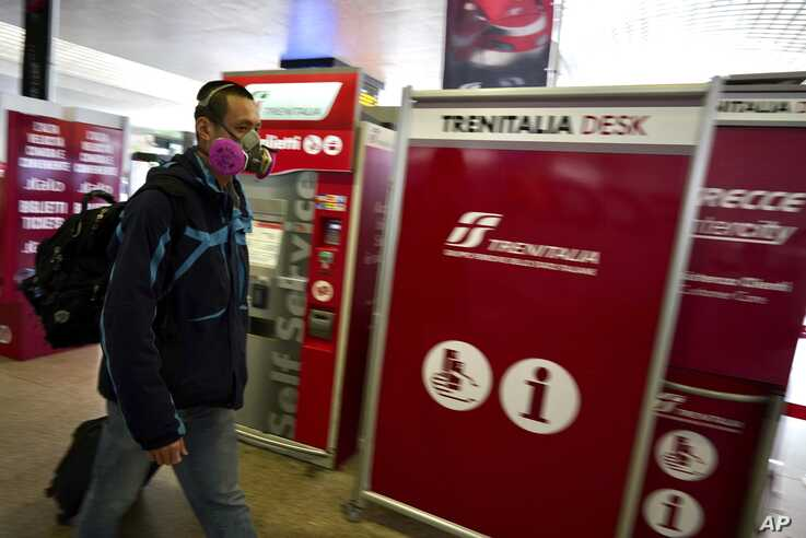 A traveler wears a mask inside Rome's Termini train station, Tuesday, March 10, 2020.